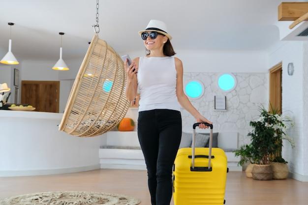Взрослая женщина с багажом с чемоданом идет в холл отеля, женщина, путешествующая с деловой поездкой