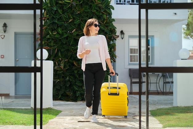 Взрослая женщина с багажом с чемоданом идет в холл отеля