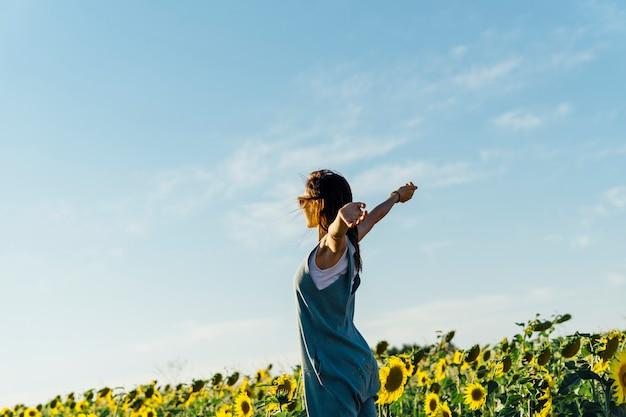 ひまわり畑で両手を広げて大人の女性。自由の感覚