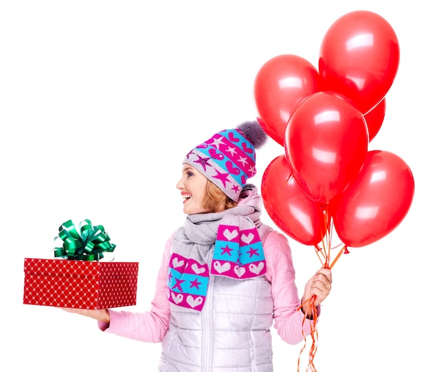 Adult woman with red gift box and balloons looking side isolated on white