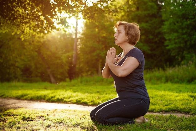 짧은 머리를 가진 성인 여성은 여름에 눈부신 태양 광선에 닫힌 눈으로 공원에서 접힌 손바닥으로 명상합니다.
