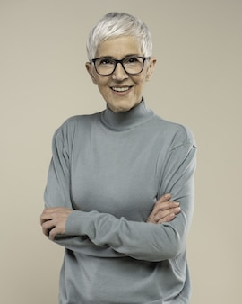 Adult woman with short white hair and glasses wearing a turtleneck and posing in a studio