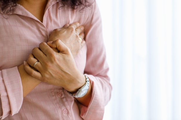 Adult woman with sudden heart attack and use hand hold chest with distorted face. concept of emergency health care and affected from congestive failure or cardiopulmonary resuscitation, heart problem.