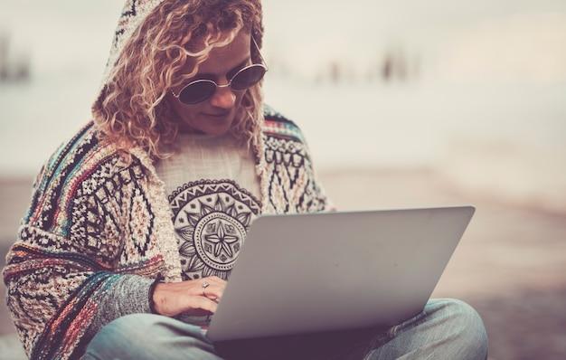 トレンディな自由奔放に生きるシックな服を着た大人の女性は、ラップトップコンピューターで屋外で無料で動作します