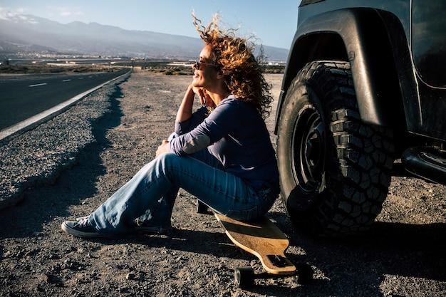 バックグラウンドで長い道のりで車の外のロングボードでウィッティング大人の女性