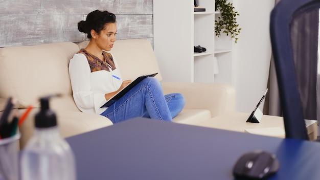 自宅からタブレットコンピュータでビデオ会議中にクリップボードにメモを書く大人の女性。