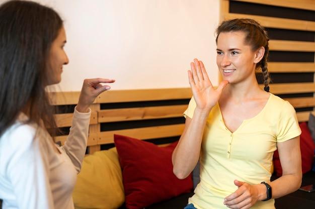 Adult women communicating through sign language
