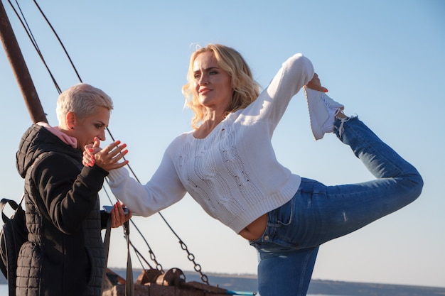 Adult women homosexual couple practice yoga on an old ship on the beach