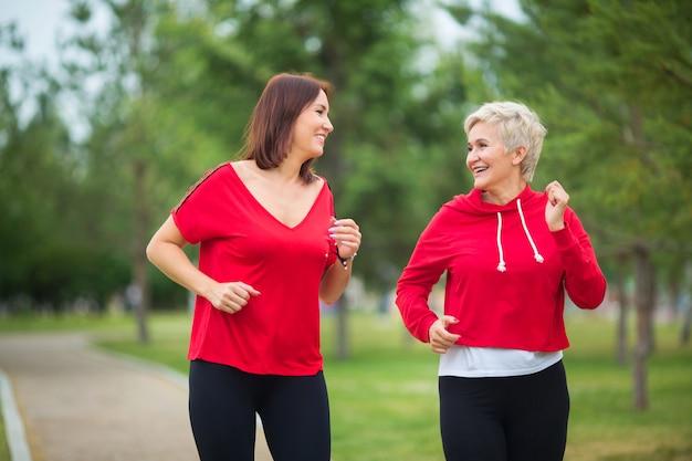 Взрослые женщины в спортивной одежде бегают в летнем парке