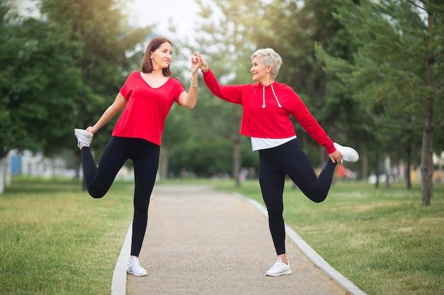 Взрослые женщины в спортивной одежде растягиваются перед бегом в парке