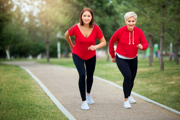 Adult women in sportswear jogging in the park