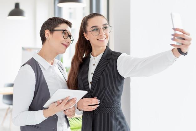 Взрослые женщины, принимающие селфи в офисе