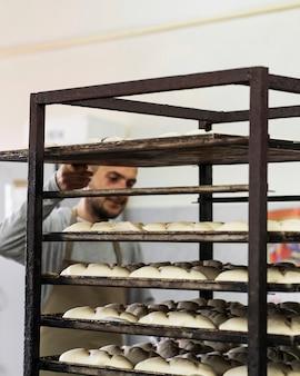 Adulto che lavora su deliziosi pani freschi