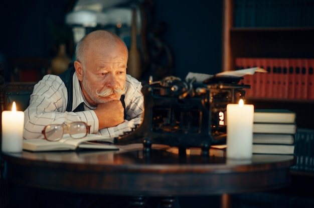 Adult writer works on typewriter with candle light