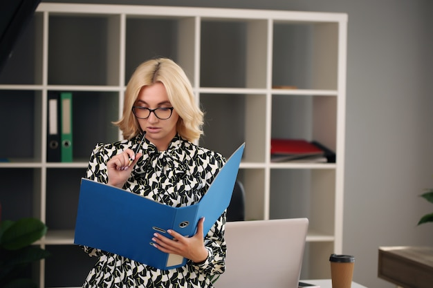 그녀의 사무실에서 일하는 성인 젊은 비즈니스 여자.