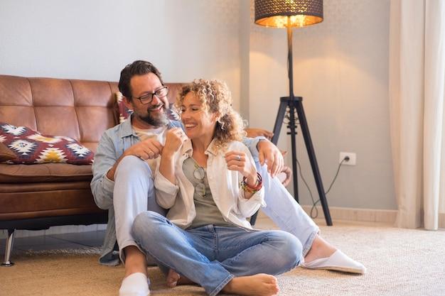 自宅の床に座って一緒に余暇の屋内活動を楽しんでいる大人の若いカップルの男性と女性-リビングルームでリラックスした時間を過ごしている愛と関係の中年の人々