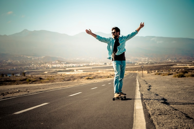 長い通りのアスファルト道路と背景の屋外の山々の長いボードテーブルで移動する大人の若い男-自由とアクティブな人々の概念