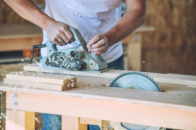 製品のツールを使用して大工の店で働く大人の若い男
