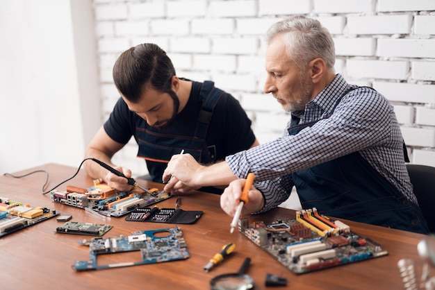 Adult and young men repair parts from the computer together