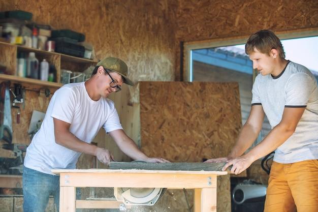 大人の若い男性、ツールを使って大工のワークショップで働く2人の労働者