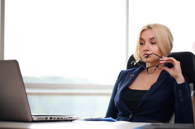 그녀의 사무실에서 일하는 성인 젊은 예쁜 비즈니스 여자. 그녀는 매우 바쁘고 덥습니다.