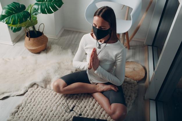 Взрослая молодая женщина в медицинской маске занимается йогой дома в гостиной с онлайн-уроками на ноутбуке