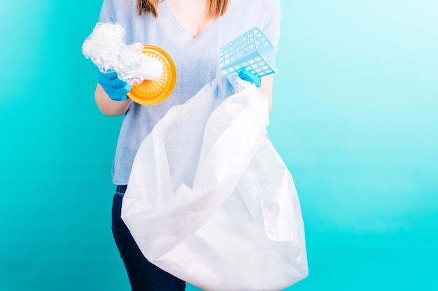 青い背景にペットボトルをリサイクルする大人の若い女性。リサイクルの概念。プラスチックフリー