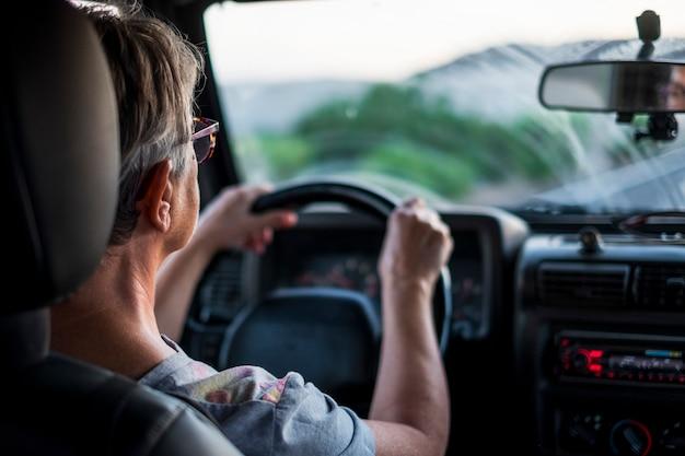 大人の白人女性が運転し、先の道を見ている
