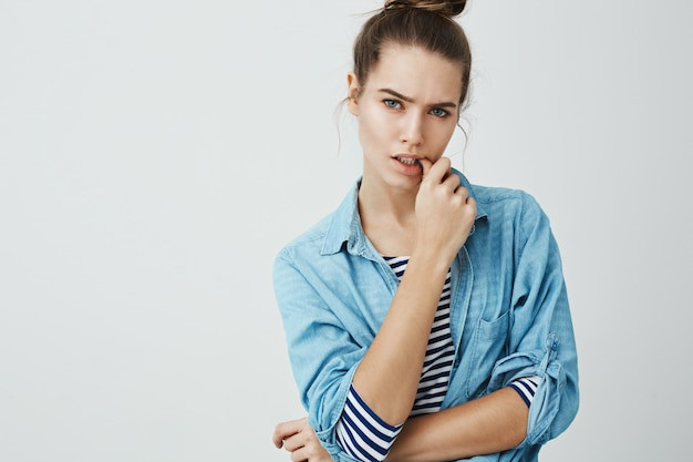 Adulthood hit me unexpectedly. studio shot of bothered and puzzled attractive woman in bun hairstyle, biting thumb while frowning and looking serious , being worried about something