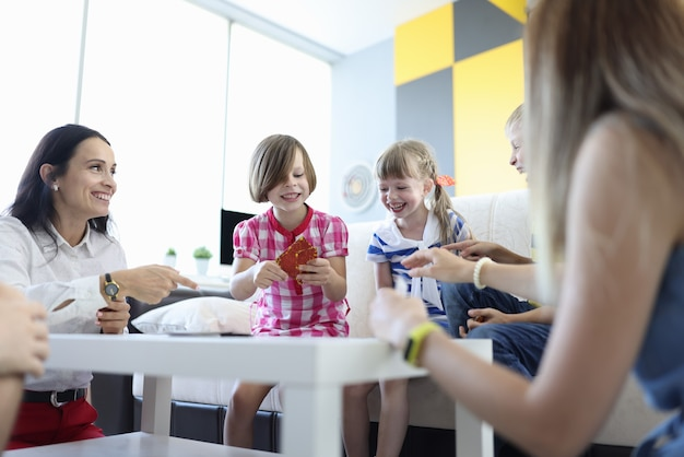 大人も子供もゲームカードを持ってテーブルの周りに座って楽しそうに笑っています。