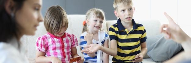 성인과 어린이는 카드 놀이가있는 테이블 주위에 앉아 소년이 주장한다