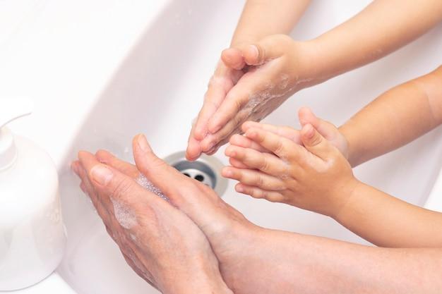 大人も子供も手を洗います。抗菌石鹸の泡で手。細菌、コロナウイルスに対する保護。手指衛生。水で手を洗う。