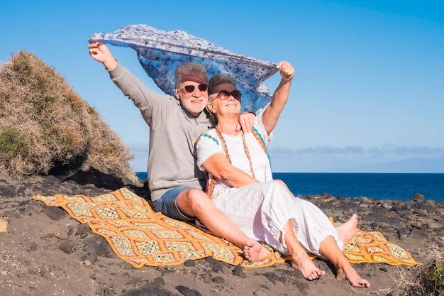 성인 백인 부부는 재미와 바다 근처의 자연 속에서 함께 야외 레저 활동을 즐길 수 있습니다-히피 자유 스타일과 은퇴 한 사람들을위한 멋진 라이프 스타일 컨셉