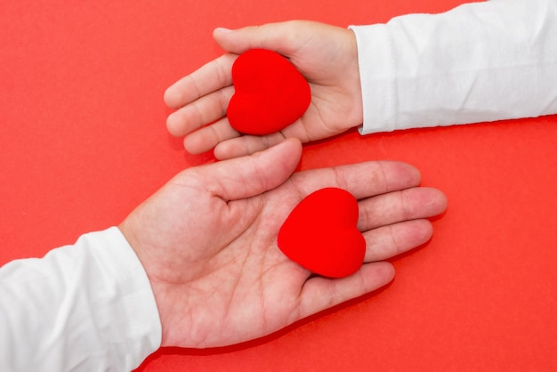 Adults and children hands holding red heart, health care love, give, hope and family concept, world heart day, world health day