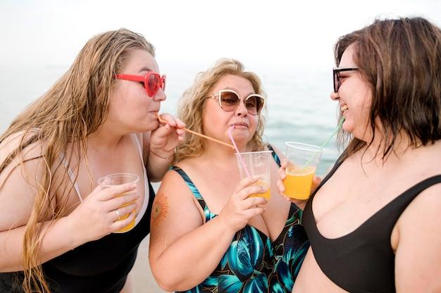 Adulti che bevono succo in spiaggia