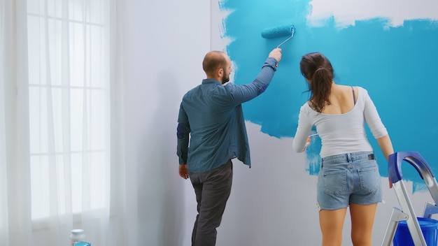 Adults renovating apartment painting wall using roller brush with blue paint. apartment redecoration and home construction while renovating and improving. repair and decorating.