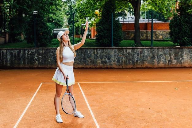 고급 자신감 있는 여성 테니스 선수가 열린 여름 공개 코트에서 공을 치고 포핸드 스윙을 합니다.