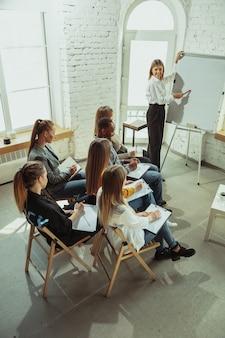 Передовой. женщина-спикер дает представление в зале на семинаре. бизнес центр. высокий угол обзора участников в аудитории. конференц-мероприятия, обучение. образование, разнообразие, инклюзивная концепция.