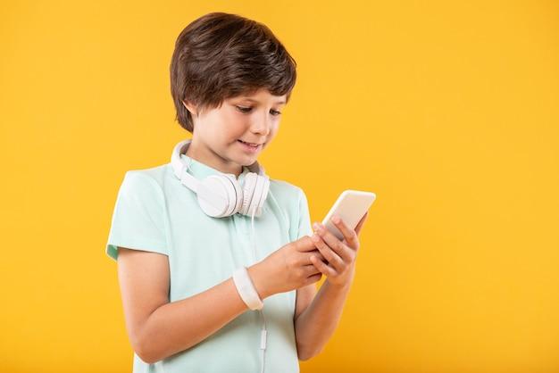 高度な技術。彼の電話を使用し、彼のヘッドフォンを身に着けているあふれんばかりの黒髪の男子生徒