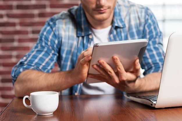 無料wi-fiの利点。彼の職場に座ってデジタルタブレットに取り組んでいる若い男のクローズアップ