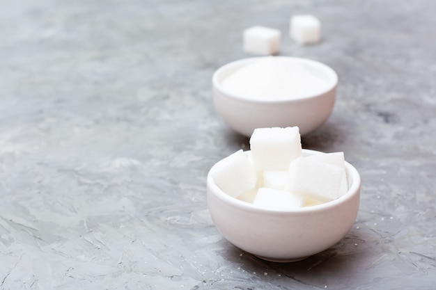 Advantages of refined sugar over granulated sugar. two types of sugar in white bowls on the table, standing next to each other