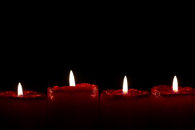 조용히 타오르는 작은 불길과 함께 4개의 빨간 크리스마스 양초가 강림합니다.