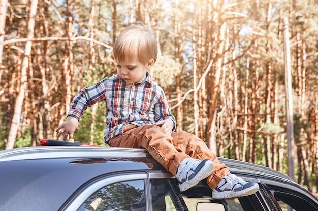 Adventure awaits cute little boy sitting on the car family road trip