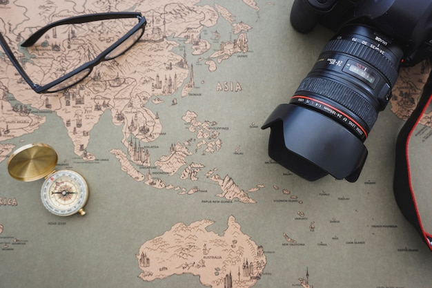 Adventure background with compass, camera and glasses