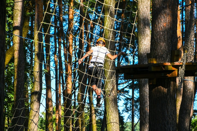 Adventure climbing high wire park. close-up. young boy in helmet having fun and playing at adventure park, holding ropes and climbing wooden stairs. active lifestyle concept. summer leisure activities