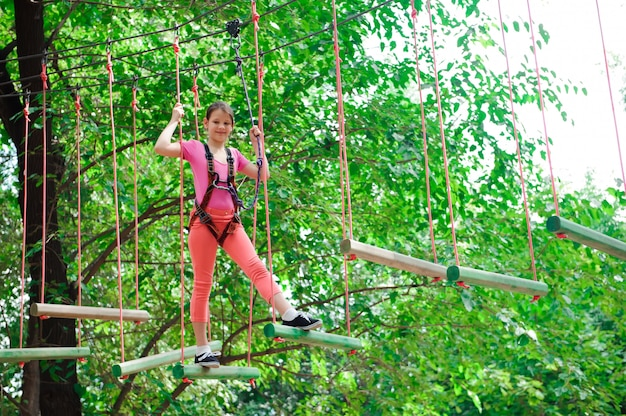 Adventure climbing high wire park - hiking in the rope park girl.
