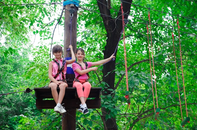 Adventure climbing high wire park - hiking in rope park two girls