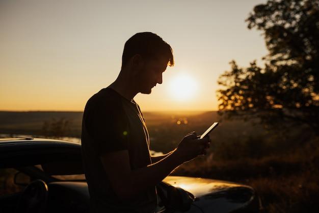 Человек путешественника исследователя приключений использует сотовый телефон в горе во время путешествия.
