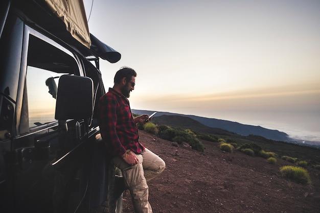 冒険探検家の旅行者の男性は、オフロードの黒い車と屋根の上のテントで旅行の遠足中に野生の山の場所でインターネット接続付きの携帯電話を使用します-無料の人々の概念