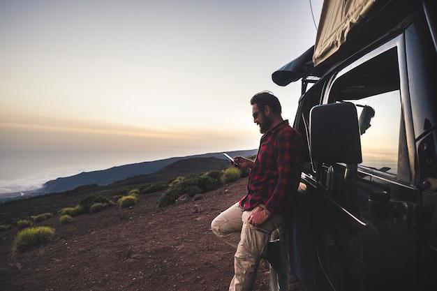 冒険探検家の旅行者の男性は、オフロードの黒い車と屋根の上のテントで旅行の遠足中に野生の山の場所でインターネット接続付きの携帯電話を使用します-フリーピープルのコンセプト